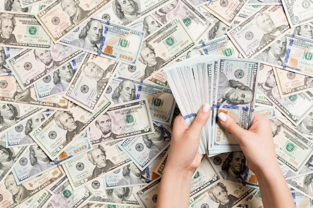 Draufsicht von den weiblichen händen, die geld auf dollarhintergrund zählen.