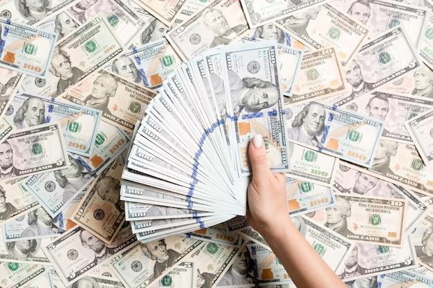 Draufsicht von den weiblichen händen, die geld auf unterschiedlichem dollarhintergrund zählen. schuld . anlagekonzept