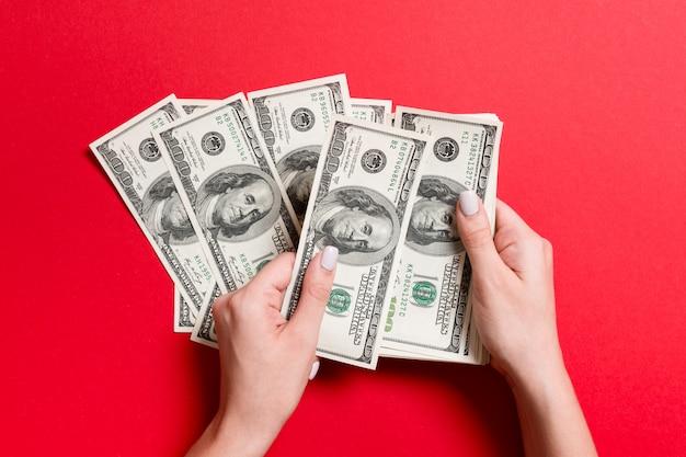 Draufsicht von den weiblichen händen, die geld zählen. hundert dollarbanknoten auf buntem hintergrund