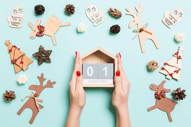 Draufsicht von den weiblichen händen, die kalender auf blau halten.