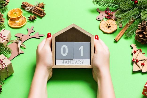 Draufsicht von den weiblichen händen, die kalender auf grünem hintergrund halten
