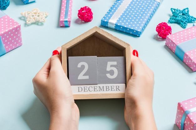 Draufsicht von den weiblichen händen, die kalender auf purpur halten.