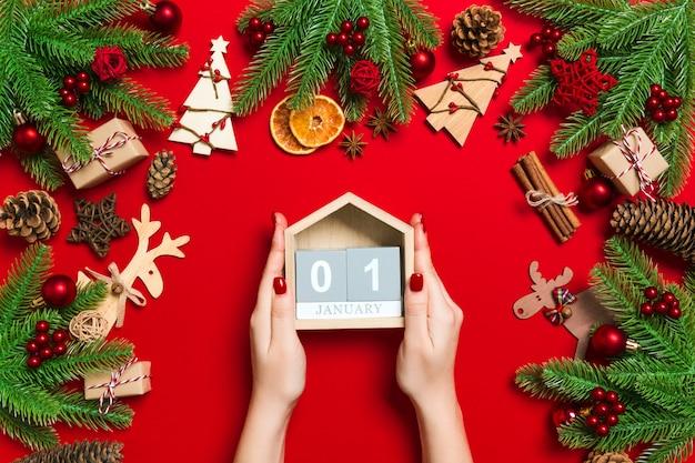 Draufsicht von den weiblichen händen, die kalender auf rot halten.