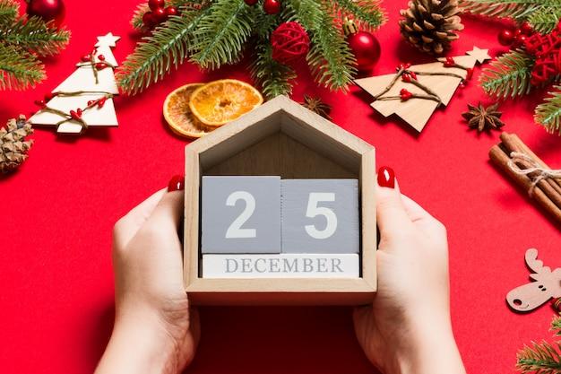 Draufsicht von den weiblichen händen, die kalender auf rotem hintergrund halten