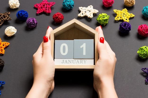 Draufsicht von den weiblichen händen, die kalender auf schwarzem hintergrund halten