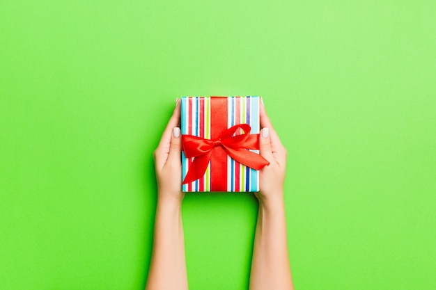 Draufsicht von den weiblichen händen, die weihnachten oder anderes handgemachtes präsentkartonpaket des feiertags auf grünem hintergrund halten
