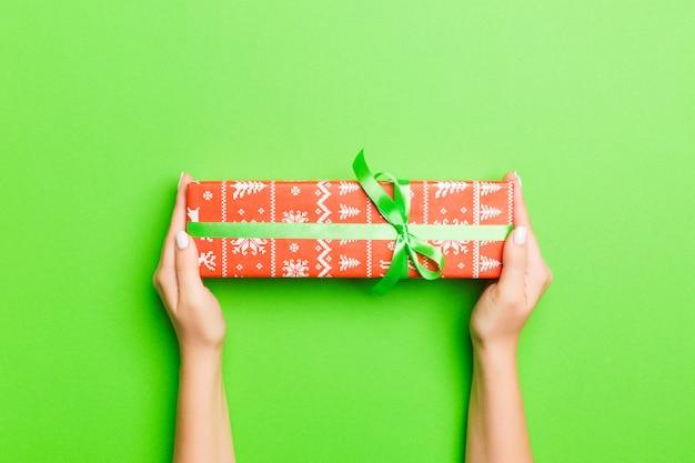 Draufsicht von den weiblichen händen, die weihnachten oder anderes handgemachtes präsentkartonpaket des feiertags in den palmen halten