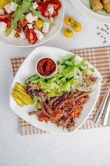 Draufsicht von dönerscheiben mit grünem salat und zwiebeln auf einem weißen teller