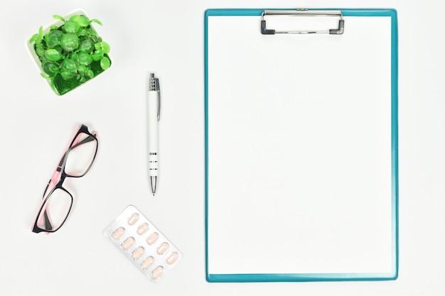 Draufsicht von doktor desk mit brille, droge, stift und klemmbrett. kopieren sie platz.