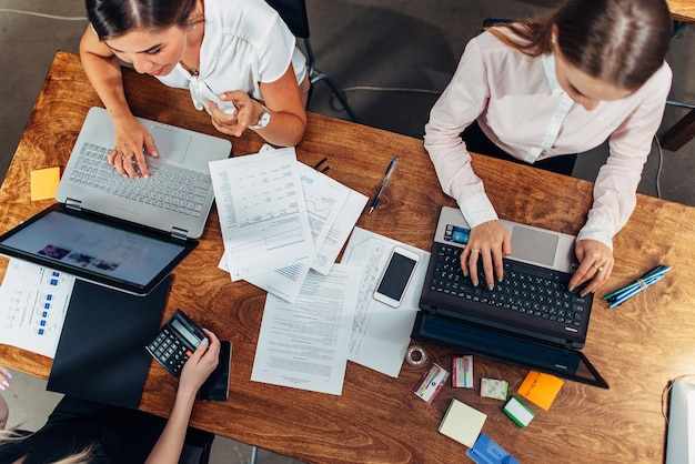 Draufsicht von drei frauen, die mit dokumenten arbeiten, die laptops verwenden, die am schreibtisch sitzen.