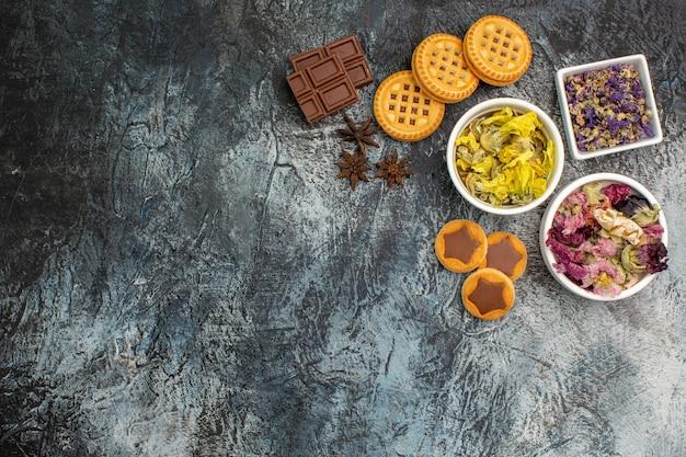 Draufsicht von drei schalen trockener blumen mit schokolade und keksen auf grauem hintergrund