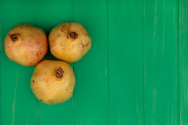 Draufsicht von drei süßen granatäpfeln lokalisiert auf einer grünen holzwand mit kopienraum