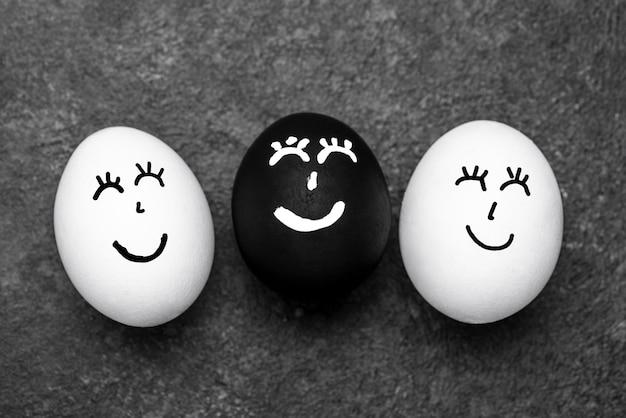 Draufsicht von drei verschiedenfarbigen eiern mit gesichtern für schwarze lebensmateriebewegung