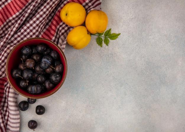 Draufsicht von dunkelvioletten sauren schlehen auf einer roten schüssel mit frischen süßen pfirsichen auf einem karierten tuch auf einem weißen hintergrund mit kopienraum