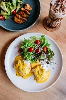 Draufsicht von egg benedict diente mit salat in der weißen platte.