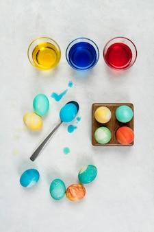 Draufsicht von eiern für ostern mit farbe in gläsern und löffel