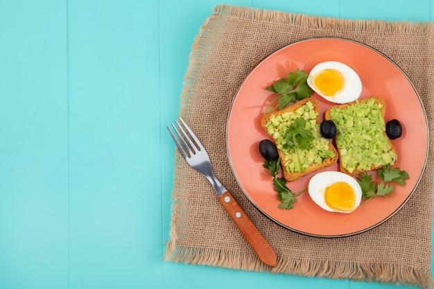 Draufsicht von eiern mit gerösteten brotscheiben mit avocadopulpe auf orangeem teller mit gabel auf sackleinen auf blau