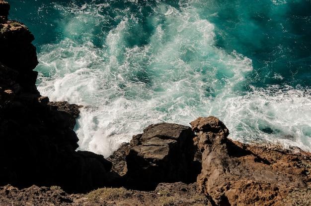 Draufsicht von einem berg der azurblauen tiefsee mit wellen unter dem klaren blauen himmel am sonnigen tag