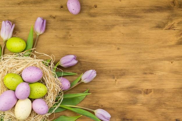 Draufsicht von einem bunten ostereiern im nest und in den lila tulpen auf braunem holzhintergrund mit nachrichtenraum