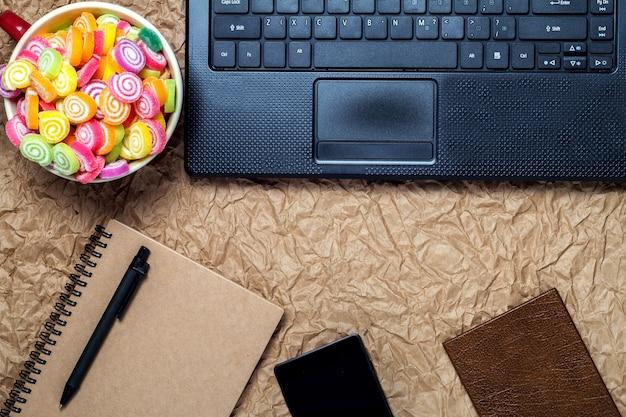 Draufsicht von einem computer, laptop, süßigkeiten, notizbuch, stift, smartphone und büroarbeitsplatz vintage-stil