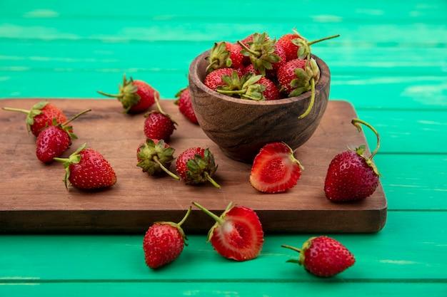 Draufsicht von erdbeeren auf einer hölzernen schüssel mit erdbeeren lokalisiert auf einem hölzernen küchenbrett auf einem grünen hintergrund