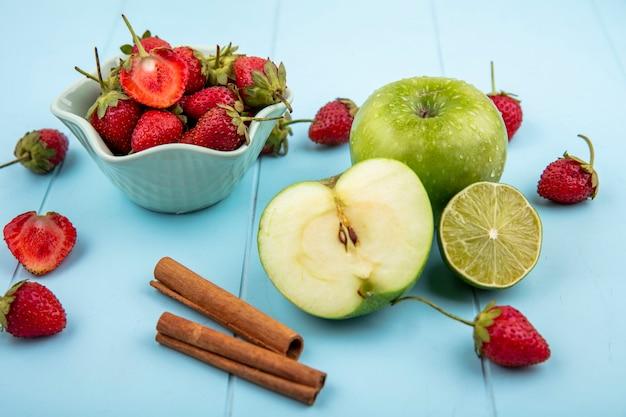 Draufsicht von erdbeeren auf einer weißen schüssel mit grünen äpfeln mit zimtstangen auf einem blauen hintergrund