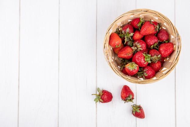 Draufsicht von erdbeeren im korb auf holzoberfläche