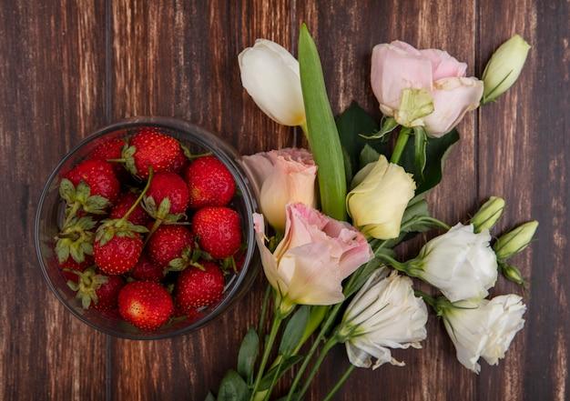 Draufsicht von erdbeeren in schüssel und blumen auf hölzernem hintergrund