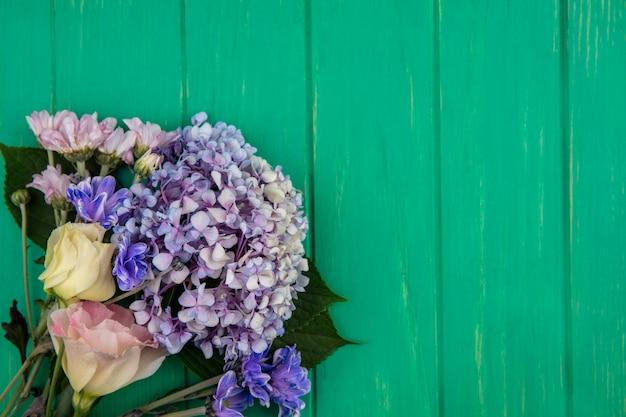 Draufsicht von erstaunlichen bunten blumen wie gardenzia gänseblümchen stieg auf einem grünen hölzernen hintergrund mit kopienraum