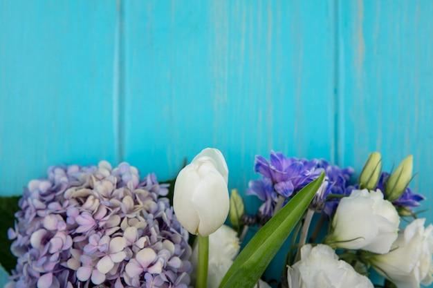 Draufsicht von erstaunlichen bunten blumen wie lila rosentulpe mit blättern auf einem blauen hintergrund mit kopienraum