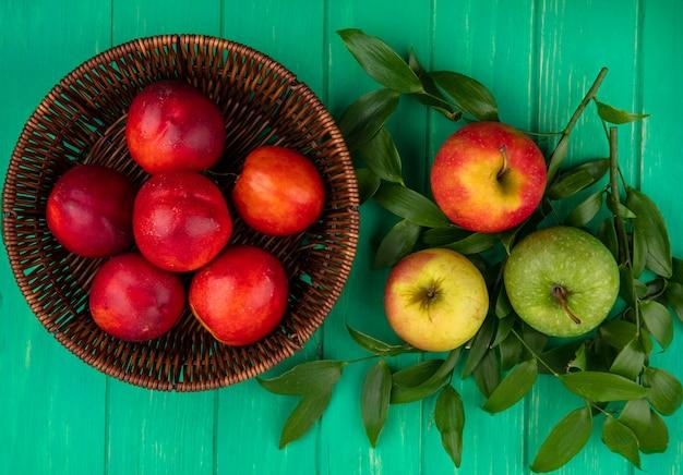 Draufsicht von farbigen äpfeln auf blattzweigen mit pfirsichen in einem korb auf einer grünen oberfläche