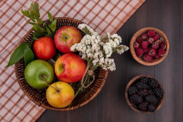 Draufsicht von farbigen äpfeln in einem korb mit weißen blumen himbeeren und brombeeren auf einer holzoberfläche