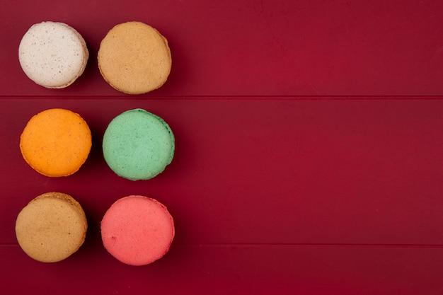 Draufsicht von farbigen macarons auf einer roten oberfläche