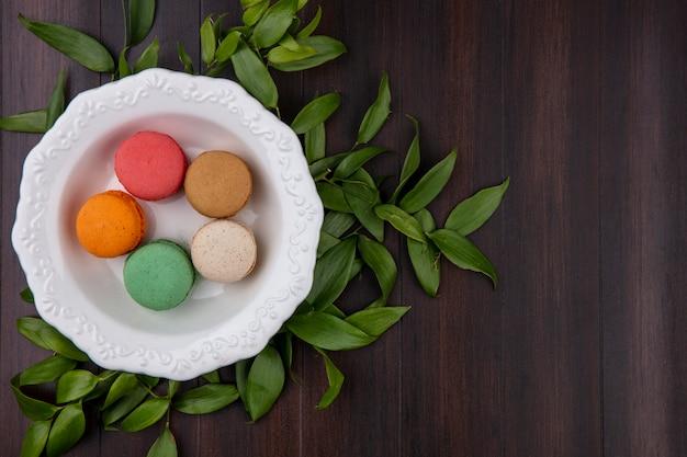 Draufsicht von farbigen macarons in einer platte mit blattzweigen auf einer holzoberfläche