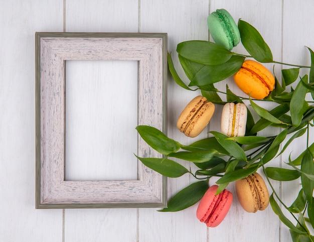 Draufsicht von farbigen macarons mit weißem rahmen und blattzweigen auf einer weißen oberfläche
