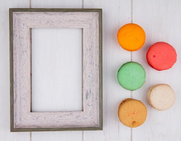 Draufsicht von farbigen macarons mit weißen rahmen auf einer weißen oberfläche
