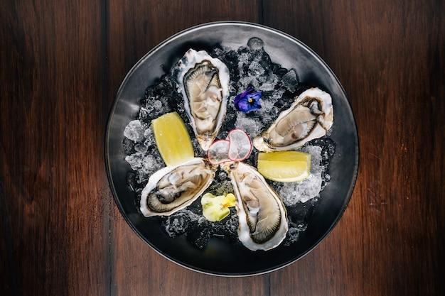 Draufsicht von feiner de claire oyster und zitrone diente in der schwarzen schüssel mit eis auf holztisch.