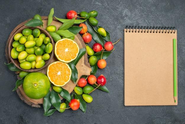 Draufsicht von fernen früchten kirschen-zitrusfrüchten mit blättern auf dem schneidebrett-notizbuchstift