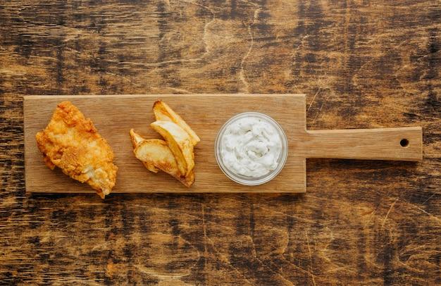 Draufsicht von fisch und chips auf schneidebrett mit soße