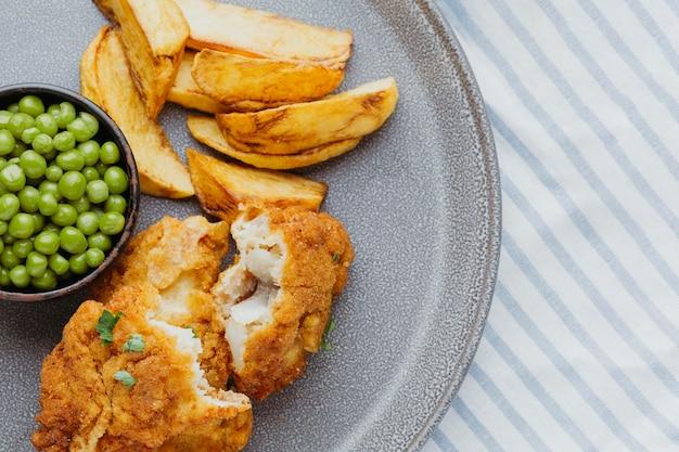 Draufsicht von fisch und chips mit erbsen auf teller