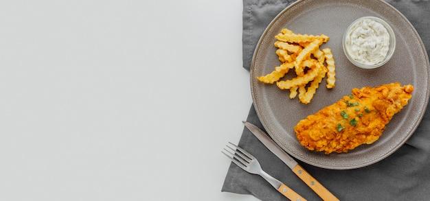 Draufsicht von fish and chips auf teller mit kopierraum