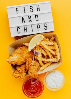 Draufsicht von fish and chips mit leuchtkasten und soße