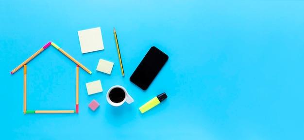 Draufsicht von fluoreszierenden markierungsstiften, die eine zeichnung eines hauses, einer tasse kaffee und eines smartphones auf pastellblauem hintergrund bilden.
