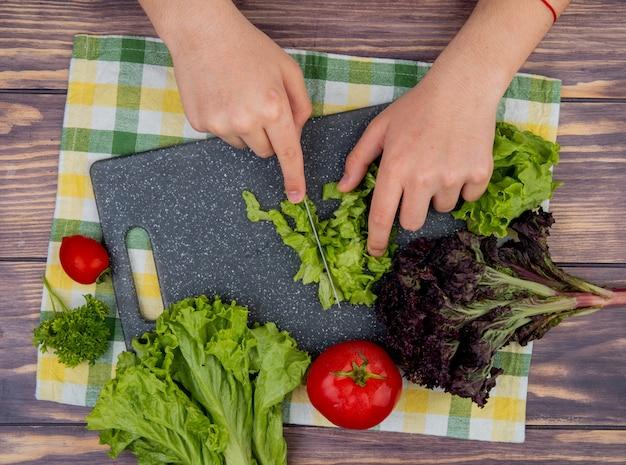 Draufsicht von frauenhänden, die salat mit messerbasilikum auf schneidebrett und tomaten auf stoff und holzoberfläche schneiden