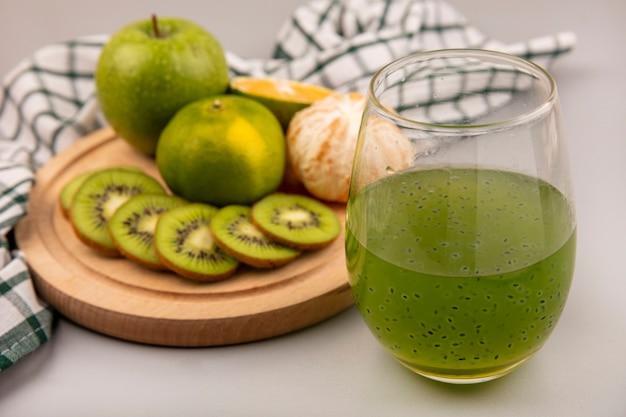 Draufsicht von frisch gehackten kiwischeiben auf einem hölzernen küchenbrett auf einem karierten tuch mit grünem apfel und mandarine mit frischem kiwisaft auf einer glasflasche