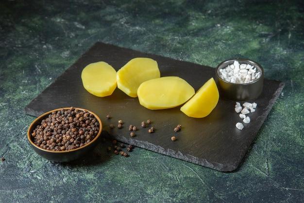 Draufsicht von frisch geschnittenen kartoffeln auf hölzernem schneidebrett und gewürzen auf grünem schwarz mischen farben mit freiem raum