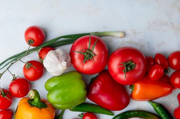 Draufsicht von frischem reifem gemüse als tomaten bunter paprika grüner chili-pfeffer knoblauch und frühlingszwiebeln auf weißem hintergrund