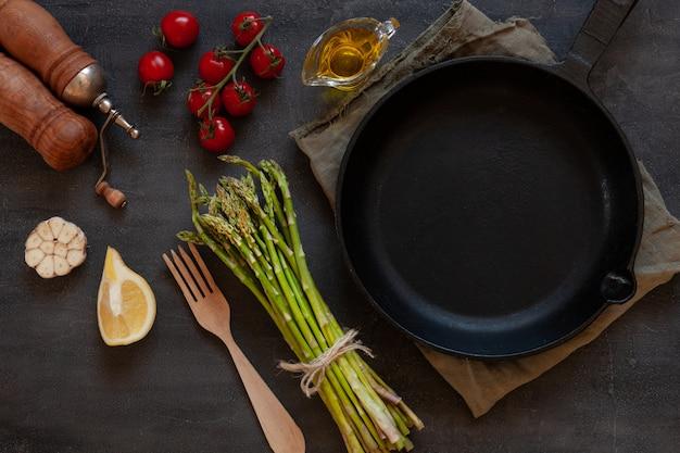 Draufsicht von frischem spargel, von olivenöl, von tomaten, von zitrone und von knoblauch mit gusseisenpfanne auf schwarzer tabelle