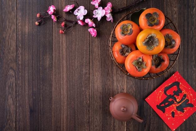 Draufsicht von frischem süßem kaki-kaki mit blättern auf holztisch für chinesisches mondneujahrskonzept, das wort bedeutet segen kommt.