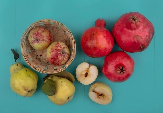 Draufsicht von frischen äpfeln auf einem eimer mit granatäpfeln und quitten lokalisiert auf einem blauen hintergrund